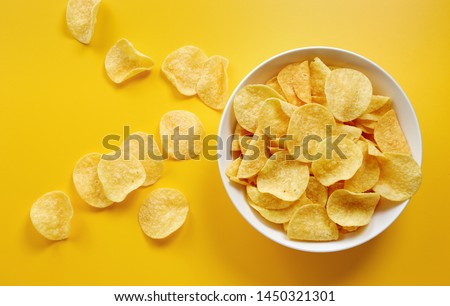Close-up of potato chips or crisps in bowl against yellow background #1450321301