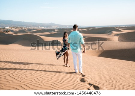 Maspalomas ,couple walking at the beach of Maspalomas Gran Canaria Spain, men and woman at the sand dunes desert of Maspalomas during a morning walk at sunrise #1450440476