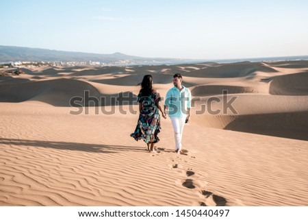 Maspalomas ,couple walking at the beach of Maspalomas Gran Canaria Spain, men and woman at the sand dunes desert of Maspalomas during a morning walk at sunrise #1450440497
