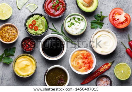 Set of different sauces in bowls and ingredients on gray rustic concrete background, top view. Tomato ketchup, mayonnaise, guacamole, mustard, soy sauce, pesto, cheese sauce - assortment of dips  #1450487015