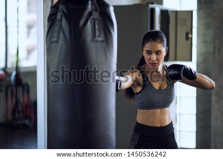 Asian Female boxer punch punching bag at fitness gym. Athletic sexy girl training Thai boxing punch and kick for bodybuilding and healthy lifestyle concept. Happy woman workout in sport club. #1450536242