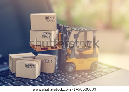 Logistics, supply chain and delivery service concept : Fork-lift truck moves a pallet with box carton. Boxes on a laptop computer, depicts wide spread of products around globe in ecommerce booming era #1450580033