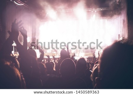 people silhouettes at the music concert. Crowd and fans showing love for the rock band at the festival #1450589363