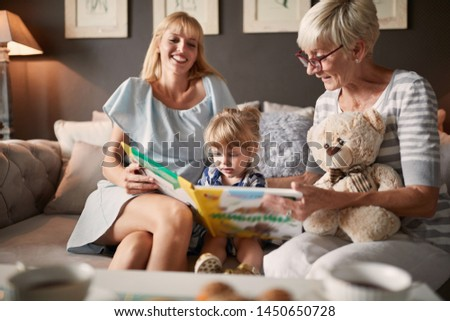 Child with mother and grandma looking picture book