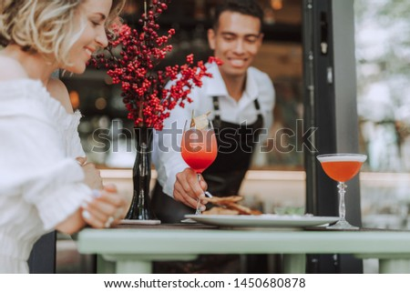Handsome barman placing glass of cocktail on table while young lady looking at it and smiling. Focus on male hand with beverage and bouquet of red berries #1450680878