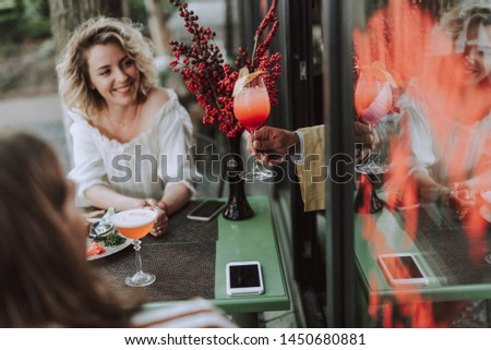 Beautiful young woman looking at glass of cocktail in bartender hand and smiling. She sitting at the table with modern smartphones and bouquet of red berries #1450680881