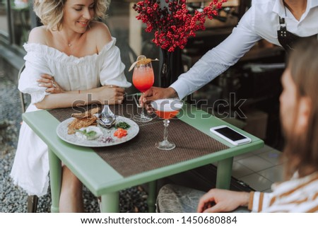 Bartender placing glass of cold drink on table while young lady looking at it and smiling. She sitting at the table with food, smartphones and bouquet of red berries #1450680884