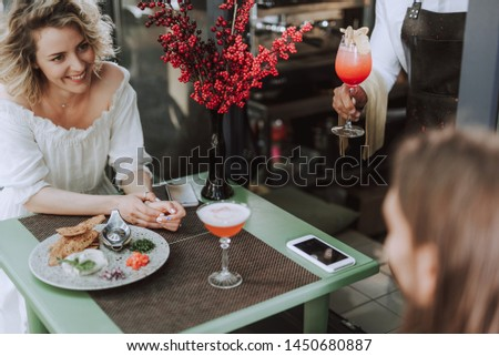 Charming blond lady looking at young man with smile while bartender holding glass of cocktail. Couple sitting at the table with food, bouquet of reed berries and smartphones #1450680887