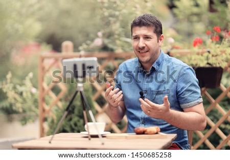 Man speaking in front of camera. Blogger man sitting on a table and making a vlog episode. Man explaining and gesturing in front of a camera.