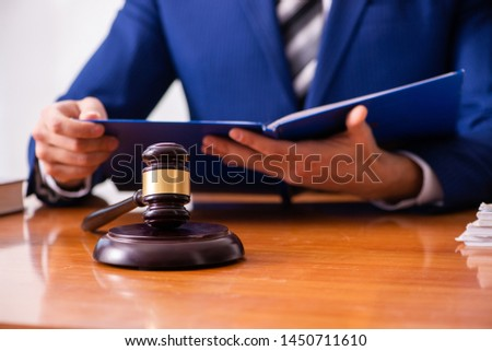 Young male judge sitting in courtroom