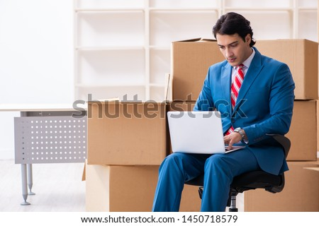 Young handsome businessman moving to new workplace  #1450718579