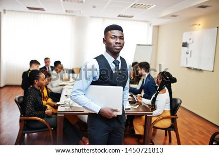 Face of handsome african business man, holding laptop on the background of business peoples multiracial team meeting, sitting in office table. #1450721813