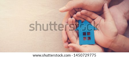 Adult and child hands holding paper house, family home, homeless shelter and real estate concept, international day of families, foster home care, family day care, social distancing #1450729775