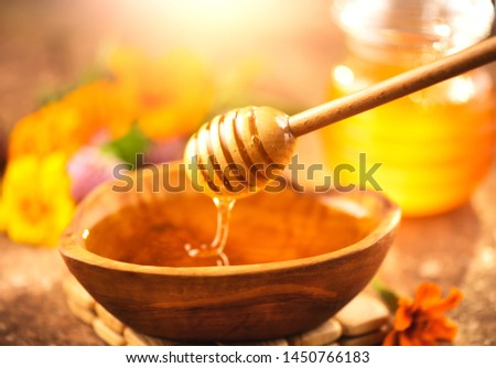 Honey dripping from honey dipper in wooden bowl.  Close-up. Healthy organic Thick honey dipping from the wooden honey spoon, closeup. Cure. Alternative medicine. Sweet dessert background #1450766183