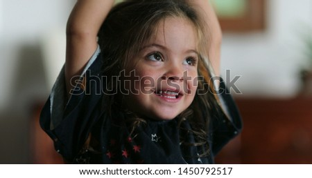 Happy portrait of little girl smiling laughing looking to camera #1450792517