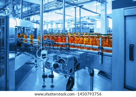 Conveyor belt, juice in bottles on beverage plant or factory interior in blue color, industrial production line, toned #1450793756