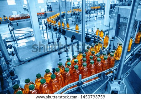 Conveyor belt, juice in bottles on beverage plant or factory interior in blue color, industrial production line, toned Royalty-Free Stock Photo #1450793759