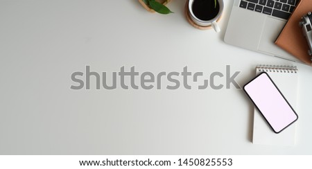 Top view of minimal workspace with blank screen smartphone, laptop on white color desk  #1450825553