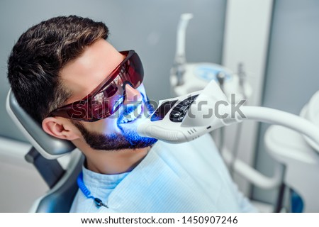 Dentist starting teeth whitening procedure with young man. #1450907246