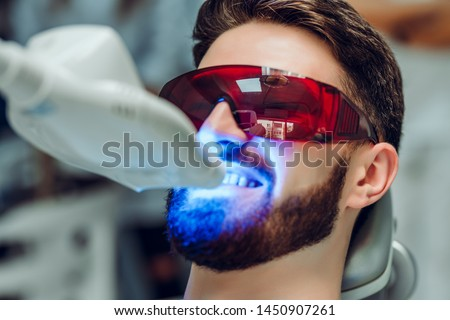 Man having teeth whitening by dental UV whitening device,dental assistant taking care of patient,eyes protected with glasses. Whitening treatment with light, laser, fluoride. #1450907261