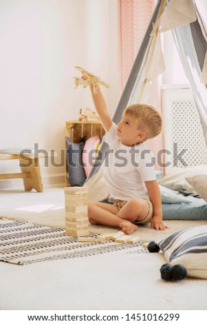 Cute little kid sitting on the floor with toy airplane in natural playroom with scandinavian tent, real photo