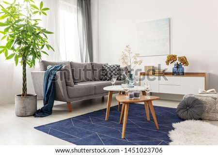 Flowers on wooden coffee table in fashionable living room interior with scandinavian design #1451023706