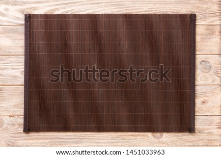 Empty Asian Food Background. Dank Bamboo mat on brown wooden background top view with copy space flat lay.