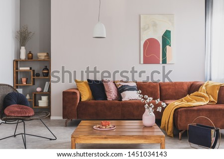 Flowers in vase on wooden coffee table in fashionable living room interior with brown corner sofa with pillows and abstract painting on the wall #1451034143