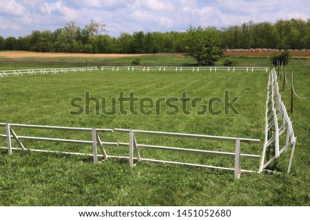 Green grass covered equestrian horse arena close up white railing borders outdoors summertime #1451052680