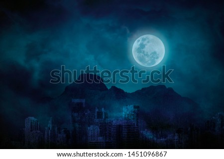 Blue full moon in city abandonment with the mountains and clouds, bright and dark at midnight, Cityscapes scary blue background