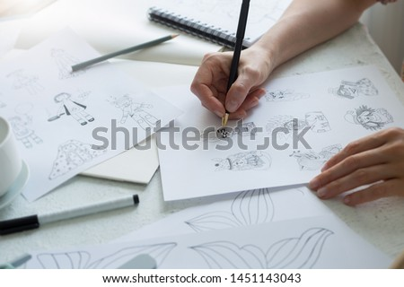 Animator designer draws sketches of various characters. Creating illustrations on paper for cartoons or video games.