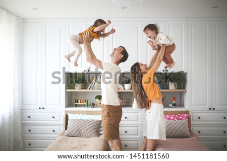 Beautiful Caucasian family with two children, dad and mom hold in their arms in the air two sisters toddlers, a child with Down syndrome in the family, a real interior #1451181560