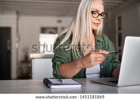 Mature woman using credit card making online payment at home. Successful old woman doing online shopping using laptop. Closeup of retired lady holding debit card for internet banking account. #1451181869