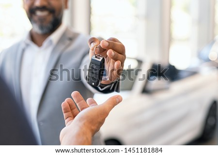 Closeup hand of cardealer giving new car key to customer. Salesman hand giving keys to a client at showroom. Man's hand receiving car keys from african agent in a auto dealership with copy space. #1451181884