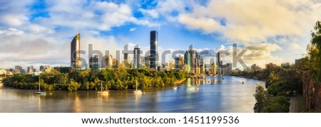 Elevated panorama of Brisbane city CBD surrounded by waters of Brisbane river from Cliffs park in soft morning light after rain. #1451199536