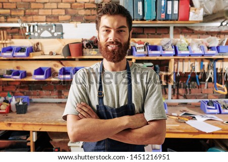 Portrait of handsome smiling bearded carpenter standing with his arms crossed and looking at camera #1451216951