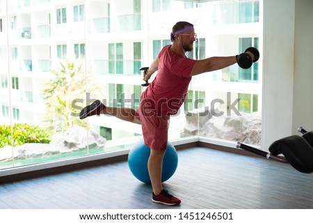 Funny fat male in pink glasses and in a pink t-shirt is engaged with dumbbells on a fit ball in the gym depicting a girl. #1451246501