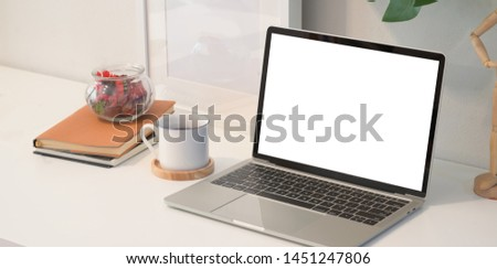 Blank screen laptop on white wooden desk in creative studio with decorations  #1451247806