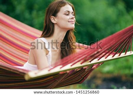 Pretty woman lying in a hammock leisure landscape leisure nature #1451256860