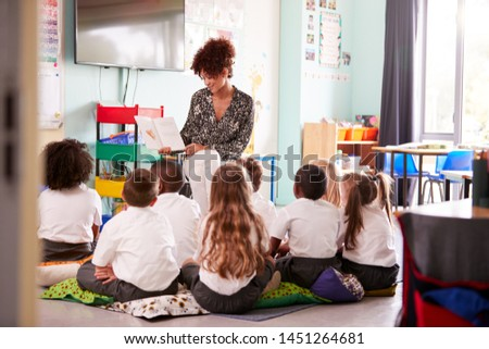 Female Teacher Reading Story To Group Of Elementary Pupils Wearing Uniform In School Classroom Royalty-Free Stock Photo #1451264681