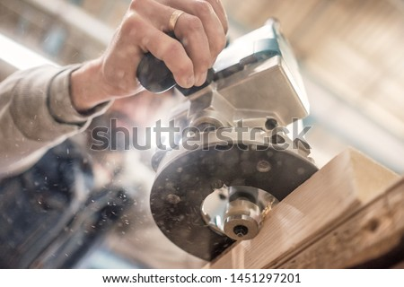 Carpenter using electric woodworking. Routing is a high speed process of cutting, trimming, and shaping wood #1451297201