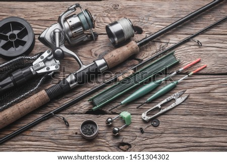 Fishing tackle for fishing peaceful fish. Float, fishing rod, reel, fishing line on the wooden background #1451304302