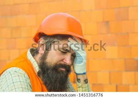 Tired builder. Construction site. Hard work. Earnings abroad. Fatigue. The builder has a headache. Production noise. #1451316776