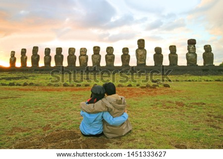 Couple having a happy moment in front of the awesome Moai statues of Ahu Tongariki at sunrise, Archaeological site in Easter Island, Chile #1451333627
