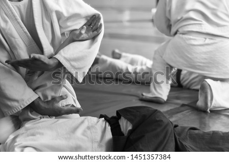 Black and white image of aikido. Hands of fighters. The traditional form of clothing in Aikido. Background image. No faces and recognizable elements Royalty-Free Stock Photo #1451357384