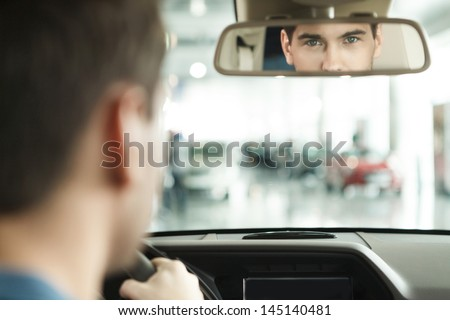 I am sure with my car choise. Hansome young men sitting at front seat of the car looking at review mirror #145140481