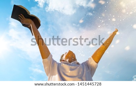 Young man in white shirt holding open book on blue sky background #1451445728