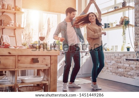 Two hearts filled with love. Full length of beautiful young couple in casual clothing dancing and smiling while standing in the kitchen at home #1451449286