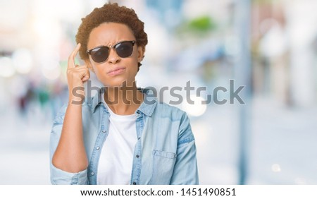 Beautiful young african american woman wearing sunglasses over isolated background with hand on chin thinking about question, pensive expression. Smiling with thoughtful face. Doubt concept. #1451490851