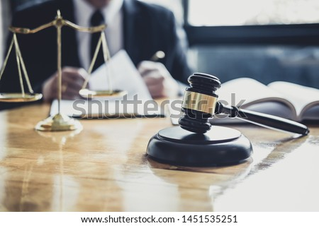 Male lawyer or judge working with contract papers, Law books and wooden gavel on table in courtroom, Justice lawyers at law firm, Law and Legal services concept. #1451535251